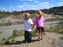 See the truck. Little brother pointing to a truck working in a sand pit across the highway Stock Photo