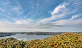 See umgeben durch Fall-Bäume und Whispy Wolken Stockfotos