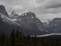 See und Schnee bedeckten Berge am stürmischen Tag mit einer Kappe Stockbilder
