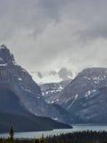 See und Schnee bedeckten Berge am stürmischen Tag mit einer Kappe Stockfoto