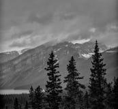 See und Schnee bedeckten Berge am stürmischen Tag mit einer Kappe Stockbild