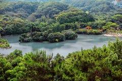 See unter üppigen grünen Bäumen und Hügeln Stockfoto