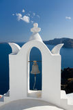 See view through church arch bell Santorini Greece. See view and cloudy sky through traditional white church arch and bell in village Oia of Cyclades Island Stock Image
