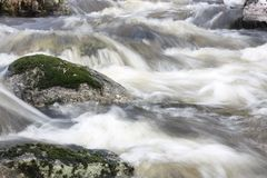 Wild river with blocking rocks stock images