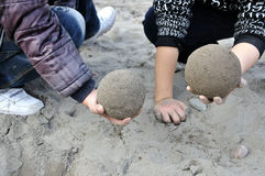 See who rub sand ball more round. Two children in the sand comparing who rub sand ball more round Stock Image