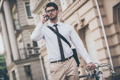 See you in office!. Confident young man in glasses talking on mobile phone and holding hand on his bicycle while standing outdoors Stock Photo