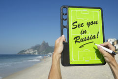See You In Russia Soccer Football Tactics Board Rio de Janeiro. Hands holding soccer football tactics board and pen with See You In Russia message on Ipanema Stock Image