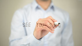 See You Soon, man writing on transparent screen. High quality stock photo