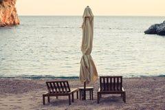 Seeansicht über den Strand, mit sunbeds und Regenschirm Stockbilder