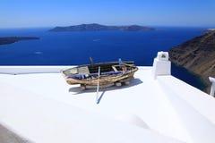 Seeansicht und ein altes Boot auf einem Dach auf Santorini stockfotografie