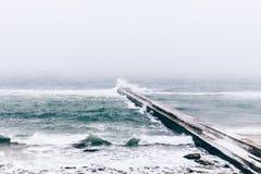 Seeansicht und ein gefrorener Pier im Winter während Schneefälle Lizenzfreies Stockbild