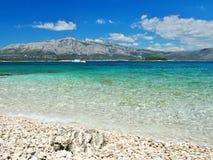 Seeansicht vom Strand mit Segelboot und Bergen Stockfotos