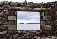 Seeansicht von einem Steinfenster einer alten Ruine nahe dem Ozean Stockbild