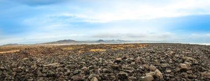 Seeansicht von Hügeln, von Himmel und von Felsen Stockfotos