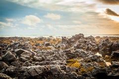 Seeansicht von Hügeln, von Himmel und von Felsen Lizenzfreies Stockbild