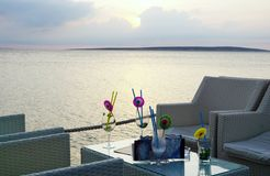 Seeansichtlounge bar bei Sonnenuntergang mit leeren Gläsern auf dem Tisch lizenzfreie stockfotografie