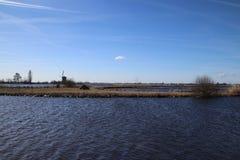 Seebereich von Oude Ade im Bereich Nordholland mit Windmühle Stockbild