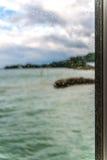 Seeblick durch ein Fenster mit nassem Glas Stockfotografie