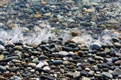 Seebrandung mit Schaum bewegt auf felsiges Ufer wellenartig Stockfotos