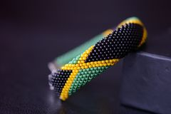 Seed beads bracelet Jamaican flag on a dark background. Close up royalty free stock photo