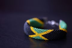 Seed beads bracelet Jamaican flag on a dark background. Close up stock image