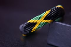 Seed beads bracelet Jamaican flag on a dark background. Close up royalty free stock images