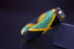 Seed beads bracelet Jamaican flag on a dark background. Close up royalty free stock photography
