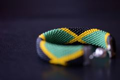 Seed beads bracelet Jamaican flag on a dark background. Close up stock images