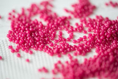 Seed beads of crimson color on the textile background Royalty Free Stock Photo