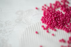 Seed beads of crimson color on the textile background Royalty Free Stock Images