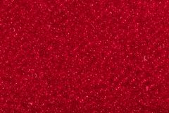 Seed beads of dark red color on the textile background. Royalty Free Stock Photography