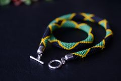 Seed beads necklace Jamaican flag on a dark background. Close up stock photo