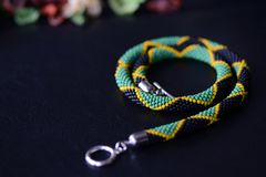 Seed beads necklace Jamaican flag on a dark background. Close up royalty free stock photography