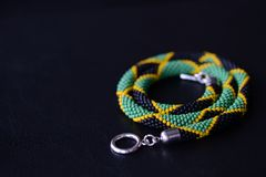 Seed beads necklace Jamaican flag on a dark background. Close up royalty free stock image