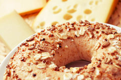 Seed brown bagel. A brown bagel topped with different seeds and some pieces of different cheese, with a retro effect Stock Photos