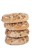 Seed brown bagels. Some brown bagels topped with different seeds, such as sesame and poppy seeds, on a white background Stock Photos