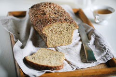 Seed crust multi grain rustic sourdough loaf, sliced at breakfast Stock Image