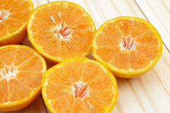 Seed (Selected focus) of orange half which is at left side of fr. Ame and other oranges on wood ground Royalty Free Stock Photo