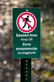 A seeded area keep off sign in french and english.  Royalty Free Stock Photo