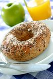 Seeded Bagel. With a glass of orange juice and a green apple stock photography