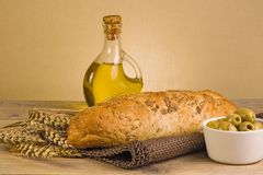 Seeded olive bread. Olive bread oil and wheat ears on a wooden board Stock Photography
