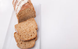 Seeded spelt loaf with honey. Close up of seeded spelt bread loaf which has been partially sliced. Spelt loaf with honey, sunflower seeds and Lupin seeds Stock Image