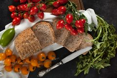 Seeded Wholemeal Loaf With Tomatoes And Chicory. Seeded wholemeal bread loaf with various types of tomatoes and raw chicory. Top view shot Royalty Free Stock Image