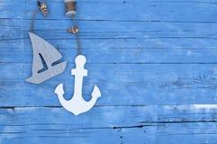 Seedekoration mit Oberteilen, Starfish, Segelschiff, Fischernetz auf blauem Antriebholz stockfotos