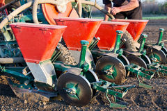 Seeder for sowing attached to tractor on soil Stock Image