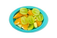 Seedless grapes orange kiwi apples cut in pieces in blue oval. Seedless grapes orange kiwi apples cut in pieces in blue oval shaped bowl or plate on isolated Royalty Free Stock Image