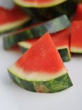 Seedless watermelon on white ceramic platter close up. Seedless pink watermelon on white ceramic platter outside with piece in front Stock Photography