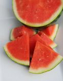 Seedless watermelon on white ceramic platter close up. Seedless pink watermelon on white ceramic platter outside with piece in front Stock Images