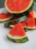 Seedless watermelon on white ceramic platter. Seedless pink watermelon on white ceramic platter outside with piece in front Stock Photos