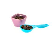Seeds of black pepper in a cup and measuring spoon Royalty Free Stock Image